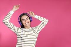 Attraktiv ung kvinna som tycker om musik i hörlurar på färgbakgrund arkivbild