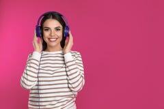 Attraktiv ung kvinna som tycker om musik i hörlurar på färgbakgrund arkivbilder