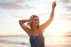 Attraktiv ung kvinna som tycker om på stranden på solnedgången royaltyfria bilder