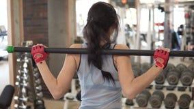 Attraktiv ung kvinna som värmer upp för en genomkörare i idrottshallen arkivfilmer