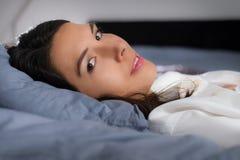 Attraktiv ung kvinna som vilar i säng Arkivfoto