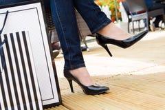 Attraktiv ung kvinnlig i sexiga svarta höga häl som tycker om ett avbrott efter lyckad shopping Royaltyfria Bilder