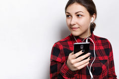 Attraktiv ung kvinnlig med mörkt hår och sund fräknig hud som bort ser med det drömlika uttryckt som lyssnar till hennes favorit  arkivfoton