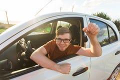 Attraktiv ung lycklig man som visar hans nya tangenter och skratta för bil Royaltyfria Foton