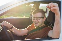 Attraktiv ung lycklig man som visar hans nya tangenter och skratta för bil Fotografering för Bildbyråer