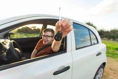Attraktiv ung lycklig man som visar hans nya tangenter och skratta för bil Royaltyfri Fotografi
