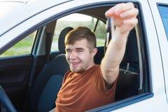 Attraktiv ung lycklig man som visar hans nya tangenter och skratta för bil Royaltyfri Bild