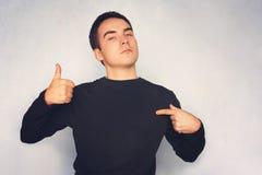 Attraktiv ung man i den vita t-skjortan som rätt pekar med hans finger Arkivbild