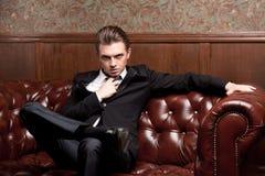 Attraktiv ung man i ett dräktsammanträde på soffan Arkivbilder