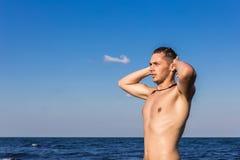 Attraktiv ung man i havet som får ut ur vatten med våta mummel Arkivbild