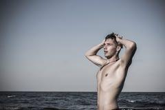 Attraktiv ung man i havet som får ut ur vatten med våta mummel Royaltyfri Foto
