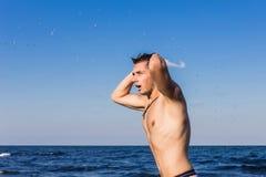 Attraktiv ung man i havet som får ut ur vatten med våta mummel Royaltyfri Bild