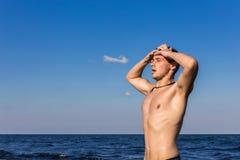 Attraktiv ung man i havet som får ut ur vatten med våta mummel Royaltyfri Fotografi