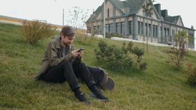 Attraktiv ung man med bärbar datorpåsen som promenerar stadsfloden och kallar på telefonen med telefonsammanträde på gräs in lager videofilmer