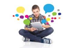 Attraktiv ung man med minnestavlan genom att använda det sociala nätverket Royaltyfri Bild