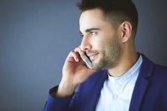 Attraktiv ung man med smartphonen på färgbakgrund royaltyfri bild