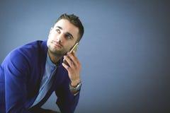 Attraktiv ung man med smartphonen på färgbakgrund arkivbild