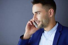 Attraktiv ung man med smartphonen på färgbakgrund royaltyfri fotografi