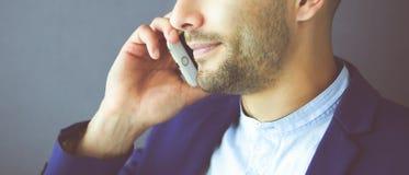Attraktiv ung man med smartphonen p? f?rgbakgrund fotografering för bildbyråer