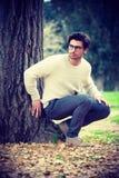 Attraktiv ung man nära ett träd i en parkera Royaltyfri Bild