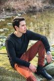 Attraktiv ung man som är utomhus- i natur, på floden royaltyfri foto