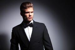 Attraktiv ung man som bär den eleganta svarta dräkten och flugan arkivbild