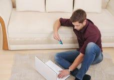 Attraktiv ung man som direktanslutet köper vid kreditkorten, medan sitta Arkivbild