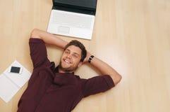 Attraktiv ung man som hemma kopplar av på trägolvet Royaltyfri Foto