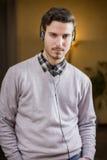 Attraktiv ung man som hemma lyssnar till musik på hörlurar Arkivfoto