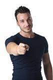 Attraktiv ung man som ler och pekar fingret på dig royaltyfri foto