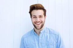 Attraktiv ung man som ler på vit bakgrund Royaltyfri Bild