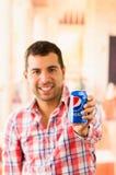 Attraktiv ung man som ler rymma en Pepsi Cola arkivfoton