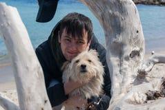 Attraktiv ung man som ligger på sandstranden med hans hund på solig dag royaltyfri fotografi