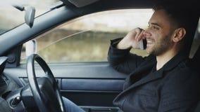 Attraktiv ung man som pratar den smarta telefonen, medan sitta inom hans bil utomhus lager videofilmer