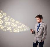 Attraktiv ung man som rymmer en telefon med meddelandesymboler Fotografering för Bildbyråer