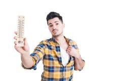 Attraktiv ung man som rymmer en termometer och svettas Royaltyfria Bilder