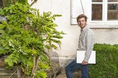 Attraktiv ung man som rymmer hans bärbar datordator i trädgården Fotografering för Bildbyråer
