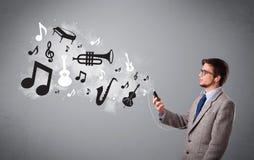 Attraktiv ung man som sjunger och lyssnar till musik med musikal Fotografering för Bildbyråer
