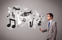 Attraktiv ung man som sjunger och lyssnar till musik med musikal Arkivfoto