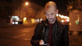 Attraktiv ung man som skrattar under en konversation på hans telefon på natten i staden lager videofilmer