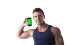 Attraktiv ung man som visar hans mobiltelefons skärmen för mellanrumsgräsplan Fotografering för Bildbyråer