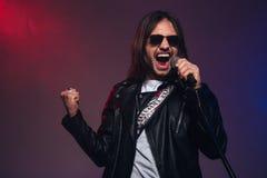 Attraktiv ung manlig sångare med långt hår som sjunger genom att använda mikrofonen Arkivfoto