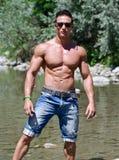 Attraktiv ung muscleman i vattendammet Arkivbild