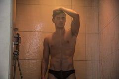 Attraktiv ung muskulös man som tar duschen royaltyfri foto