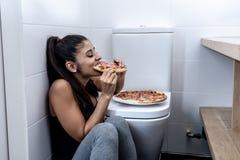 Attraktiv ung och ledsen bulimic ung kvinna som känner sig skyldigt och sjukt äta, medan sitta på golvet bredvid toaletten in royaltyfri fotografi