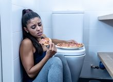 Attraktiv ung och ledsen bulimic ung kvinna som känner sig skyldigt och sjukt äta, medan sitta på golvet bredvid toaletten in royaltyfria foton