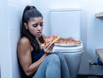 Attraktiv ung och ledsen bulimic ung kvinna som känner sig skyldigt och sjukt äta, medan sitta på golvet bredvid toaletten in arkivbilder