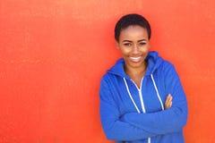 Attraktiv ung svart kvinna som ler mot röd bakgrund royaltyfria bilder