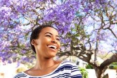 Attraktiv ung svart kvinna som utomhus skrattar vid blommaträdet arkivfoton