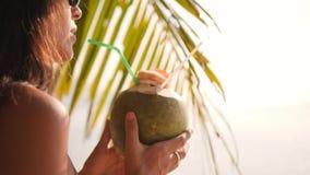 Attraktiv ung turist- Hipsterflicka för blandat lopp som dricker den nya thailändska kokosnötvattencoctailen på den tropiska stra stock video